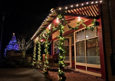 Exterior commercial restaurant decorated for Christmas with live garland lights and santas sleigh