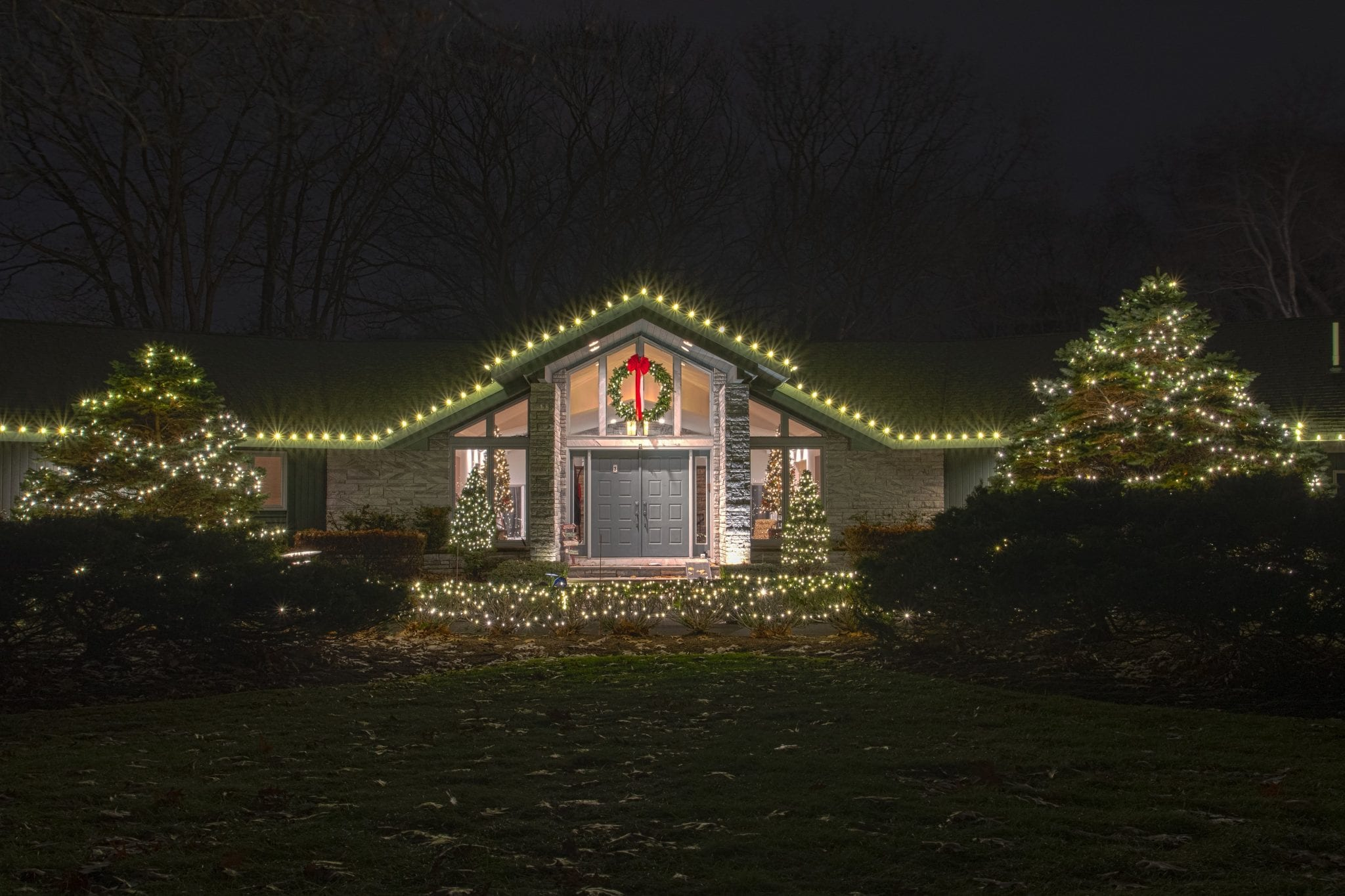 Single story home in Menands NY decorated for Christmas with white lights on the roof and trees with a live wreath hanging.