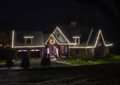 Home in Wynantskill professionally decorated for Christmas with white roof lights and a large live wreath above the entryway