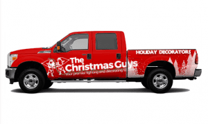 red truck wrapped with The Christmas Guys logo and words holiday decorators