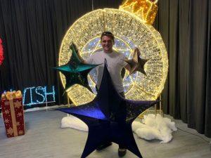 Joey Mertz holding stars for christmas decorating